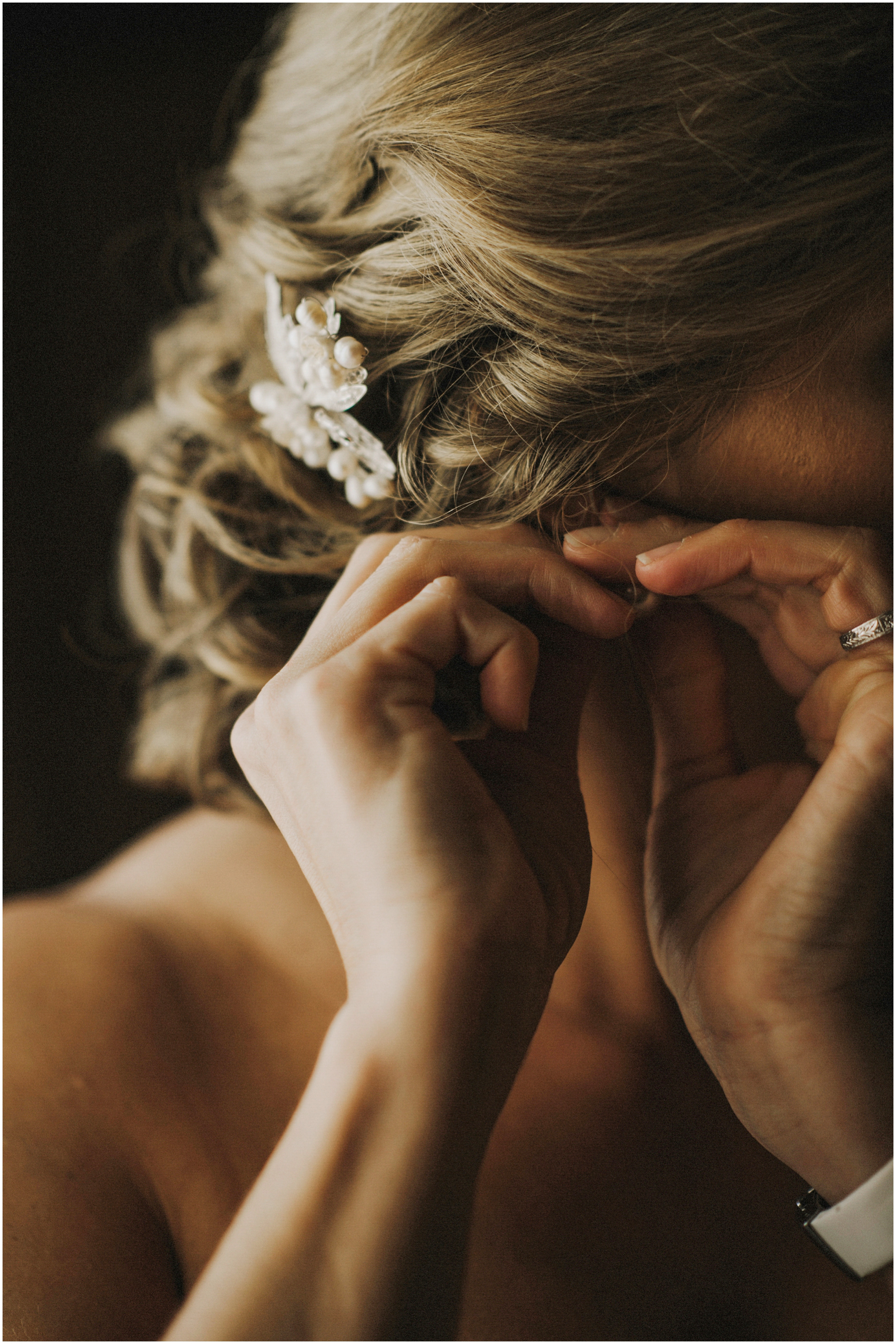 bride putting her earring on